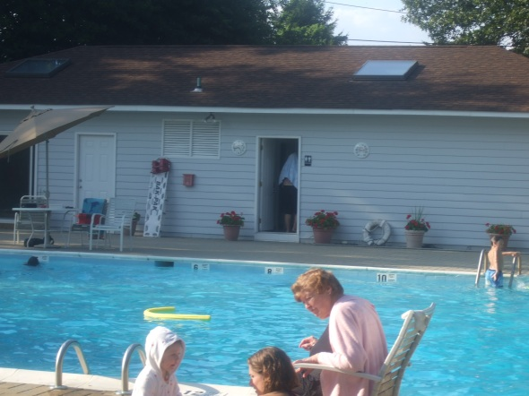Grandma Rose, Caroline and Alexa sitting poolside. Dad entering the bathroom with towel on head.